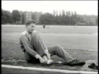 Roger Bannister wearing tracksuit putting on shoes as he sits by side of running track England 1954