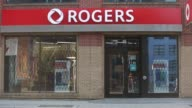 A Rogers Communications Inc sign hangs outside a building in Toronto Ontario Canada on Wednesday May 17 2017 Shots wide low angle shot of signage...