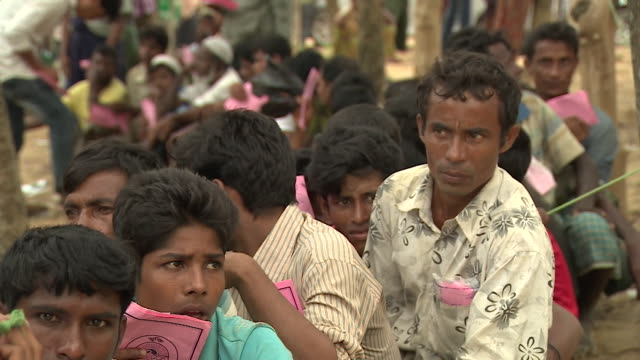 Rohingya refugees with ration cards queueing for food parcels in Bangladesh