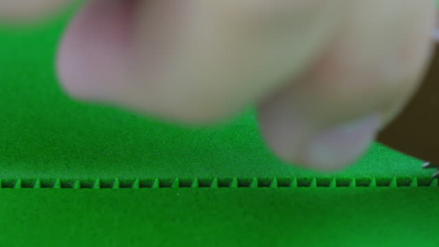 Roll and cut green color fondant into dashed lines. Close up.