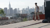 B roll clip of a young, mixed race man skateboarding through the streets of Brooklyn, NYC - slow motion.