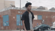B Roll of a young, mixed race man skateboarding through the streets of Brooklyn, NYC