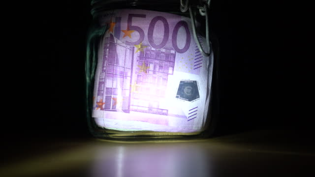 Roll of european union currency in preserving jar