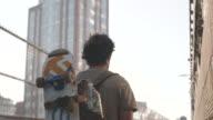B Roll shot of a skateboarder walking over NYC's Manhattan Bridge.