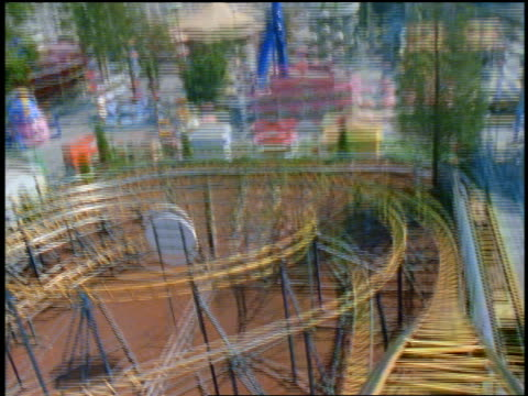 Roller coaster point of view down steep hill, around curves + up + down hills