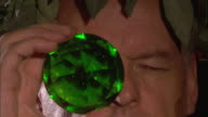 A Roman man wearing a laurel wreath turns a faceted emerald as he looks through it.
