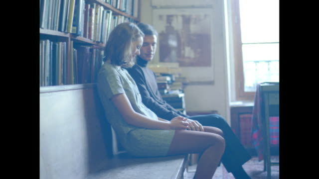 Romantic couple on a wooden bench against a book shelf wall.