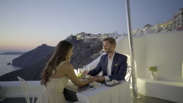 romantic dinner couple terrace restaurant santorini greece