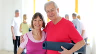 Romantic senior couple holding exercise mat in gym