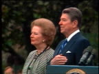 Ronald Reagan standing with hand over heart next to Margaret Thatcher