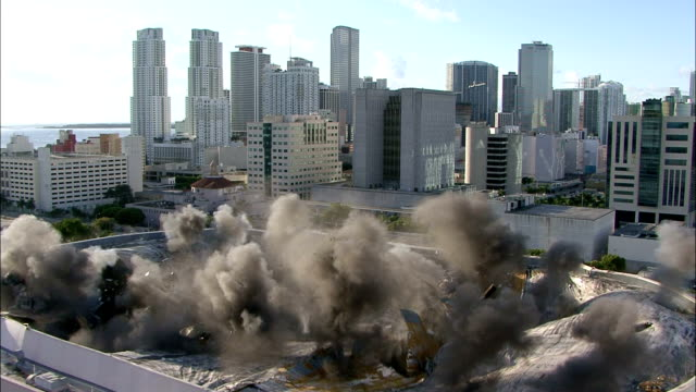 WS  Roof of a small sports arena surrounded by palm trees is demolished using explosives /  Miami, Florida, USA