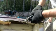 Roofer cuts roofing metal material.