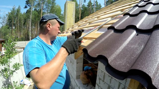 Roofer makes measurements of the roof.
