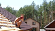 Roofer sits on the roof and performs a control measurement.
