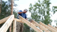 Roofer works on the roof. The builder hammers the nails with a hammer.