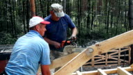 Roofers build a roof. The master works with a chainsaw.