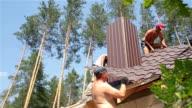 Dachdecker arbeiten auf dem Dach in der Nähe des Schornsteins.