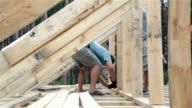 Roofers work on the roof. The builder hammers the nails with a hammer.
