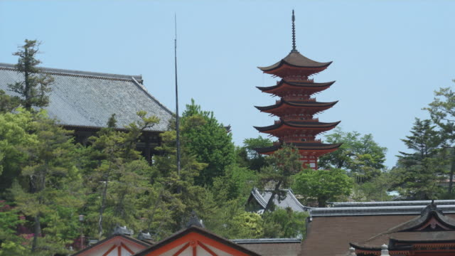 MS Roofs of buildings at Itsukushima Shrine with pagoda in background, Miyajima Island, Japan