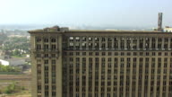 MS AERIAL Rooftop of Michigan Central Station with graffiti and broken windows / Detroit, Michigan, United States