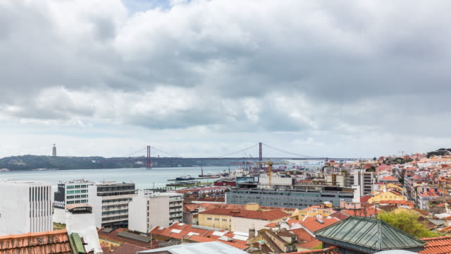 Rooftop timelapse of the Lisbon skyline with cargo seqport and the 25th of April Bridge. Portugal. April, 2017
