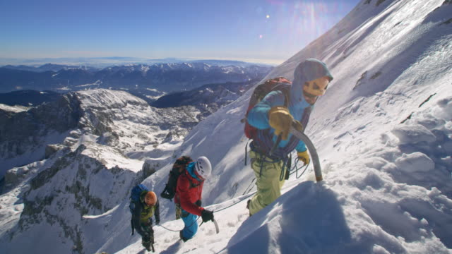 PAN Rope team mountaineers ascending the snowy mountain in sunshine