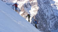 Roped up alpinists ascending the snowy mountain