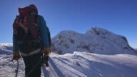 POV Roped up team of alpinists walking on a snowy mountain ridge