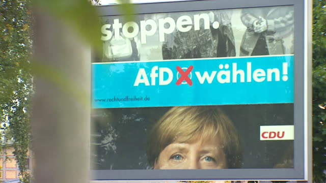 A rotating billboard displays posters for opposing political parties in the German federal election of September 2017 Angela Merkel's CDU and the AfD...