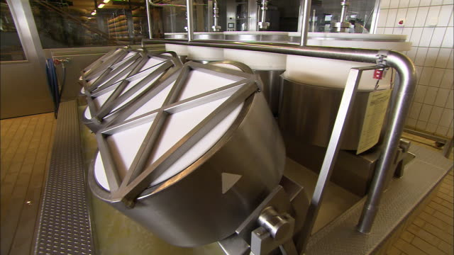 Rotating cylinders churn milk in a dairy.