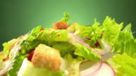 CU rotating mixed green salad garnished with croutons red onion slices and baby tomatoes