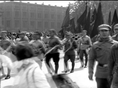 / Rotront Red Front parade truck carrying communists men carrying flags / Heinrich Thalman speaking on dais / PAN over huge densely packed crowd