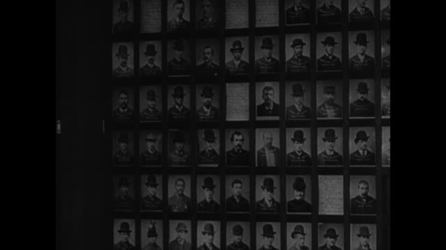 MS 'Rouges Gallery' Wall w/ photographs of arsonists criminals 1936 UPDATED Arsonists in photograph file CU Male fingers flipping through photos