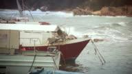 Rough sea and boats at the harbor
