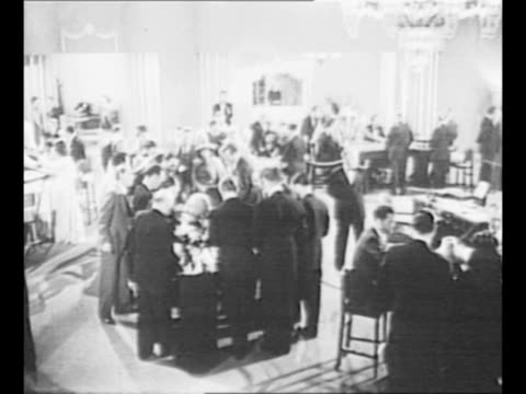 Roulette wheel spins as man in foreground faces away from camera watches wheel pan gaming table with chips as players face table in foreground and...
