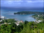 Round Hill area pan left across natural harbor surrounded by houses and hotels amongst trees blue sea and a small island in the background.