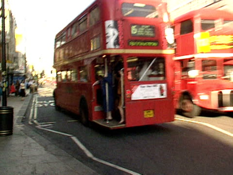 A Routemaster bus pulls up at stop and passengers alight Oxford Street 1998