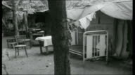 A Tale of Two Cities ** SOME Prefabricated structure moved by workers/ Temporary medical centre with women and children along/ Temporary shelter with...