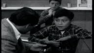 Birthday Album ITN reporter Reginald Bosanquet talking to little Red Indian boy in classroom SOT Says he is a Chippewa Indian / comes to school every...