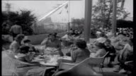 Expo 58 American tourists sitting on steps of American pavilion Woman taking off shoe American boy smiling Fountains in pond Various shots of...