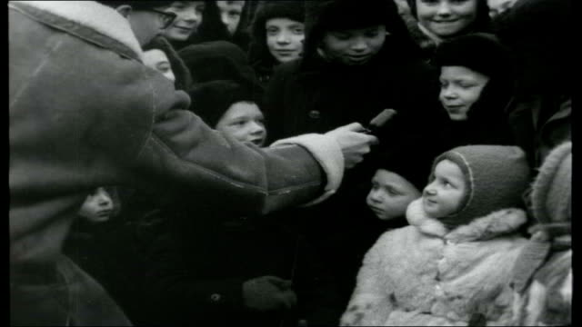 from Ballet to Ballots Children in Winter hats scarves and coats people gathered around looking at camera / Day with large group of children SOT /...