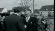 How Many Germanies Reporter to camera with East German refugees standing behind him / Smartly dressed East German man interview SOT Says he has been...