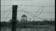 Iron Curtain Watchtower near beach with barbed wire border fence in foreground