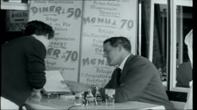 Ostend Joke scene involving 'Channel swimming' man seated at cafe and looking at set menus in windowthen speaking to waitress and rejecting Belgian...