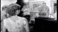 Return to the Riviera INT SEQUENCE antique shop with people looking round Shop owner Georges Barrie showing people round exhibition of young artists...