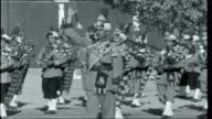 Round The World 1 PAKISTAN Karachi Bagpipe band of the Pakistan Army marching and playing SOT Men sitting watching the marching band