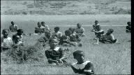 Swaziland Young Swazi children at school singing traditional song and doing accompanying movements some sitting on grass some on school verandah SOT