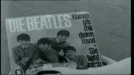 The city where the Beatles got their break Peter Penner combing his hair forward to create a Beatles moptop Young woman buying Beatles record from...