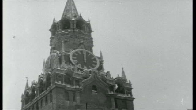 Visit to Moscow Title Sequence FEDERATION Moscow Red Square EXT / SNOW Kremlin covered in snow Clock face on clock tower above Kremlin entrance PULL...
