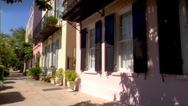 HD Row houses historical homes along sidewalk pastel colors restored urban homes some w/ wrought iron balconies No people